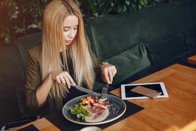Elegante empresaria sentada en un café
