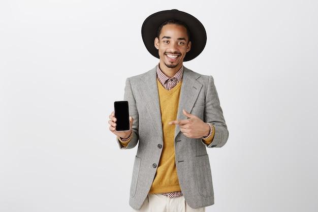 Elegante empresario afroamericano que señala el dedo en la pantalla del teléfono inteligente, mostrando la aplicación
