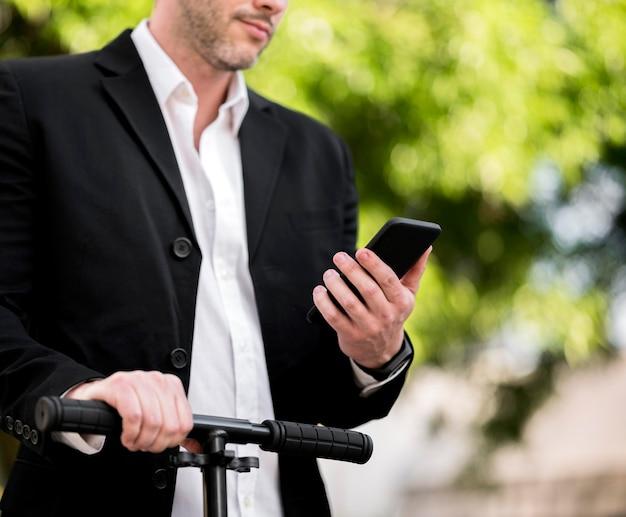 Elegante empresario montando scooter al aire libre
