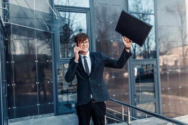 Elegante empresario de negocios con gafas, hablando por teléfono cerca del edificio de cristal del centro de negocios