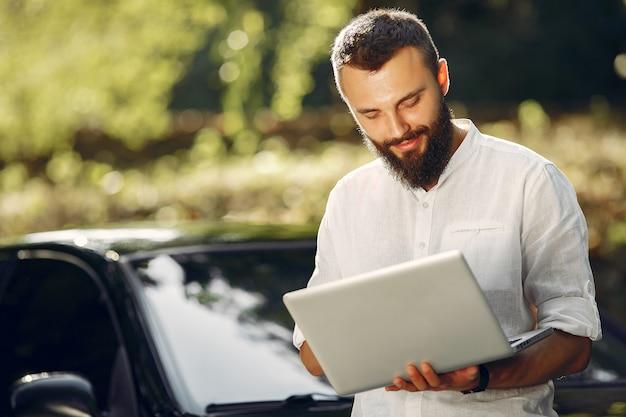 Elegante empresario de pie cerca del coche y usar la computadora portátil