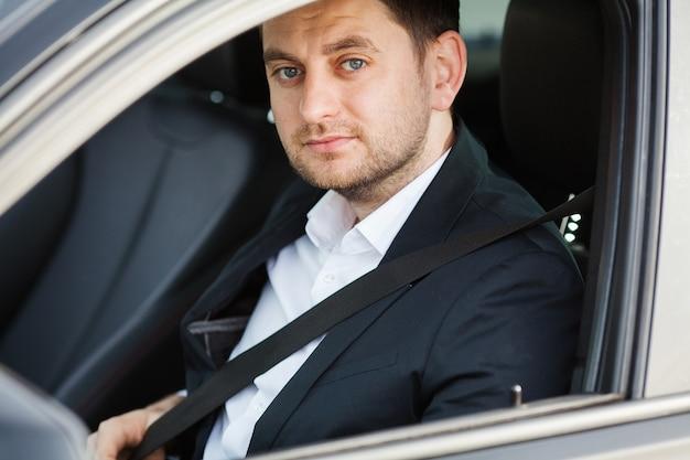 Elegante empresario vestido con el traje que se abrocha el cinturón de seguridad antes de conducir su automóvil