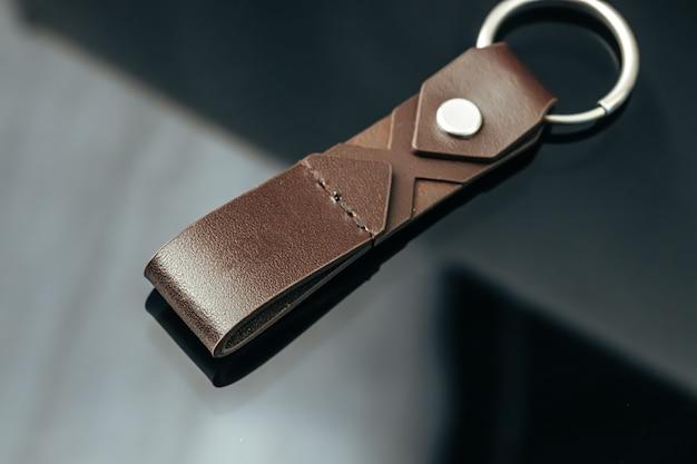 Elegante encanto de llave de metal masculino sobre fondo de cristal negro de cerca