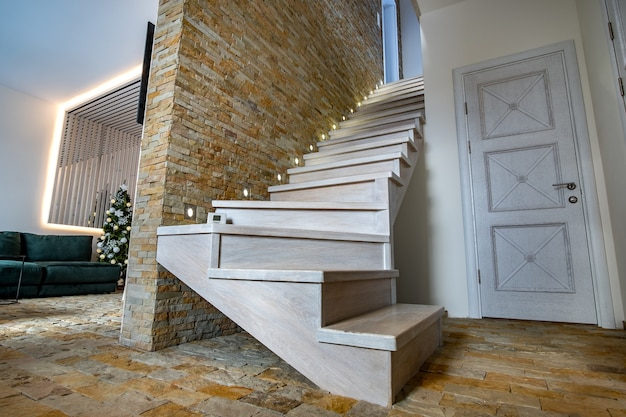 Elegante escalera de madera contemporánea dentro del interior de la casa tipo loft.