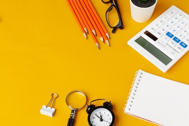 Elegante escritorio amarillo desordenado con vista superior de varios artículos de papelería