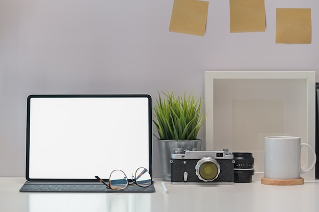 Elegante escritorio de trabajo, cámara vintage, tableta de pantalla en blanco y gadget.