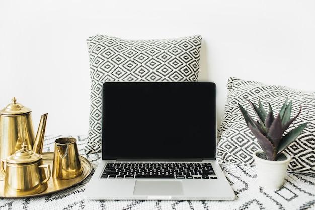 Elegante espacio de trabajo de escritorio de oficina en casa con vista frontal, computadora portátil con pantalla en blanco, tetera dorada en la bandeja y suculenta