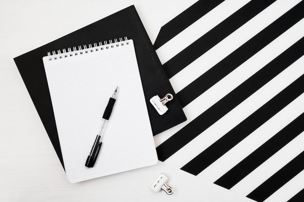 Elegante espacio de trabajo minimalista con maqueta de cuaderno, lápiz sobre rayas en blanco y negro ba