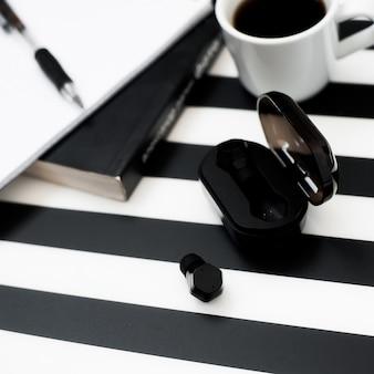 Elegante espacio de trabajo minimalista con maqueta portátil, lápiz, taza de café, auricular inalámbrico