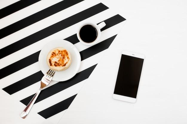 Elegante espacio de trabajo minimalista con maqueta de smartphone, libro, cuaderno, lápiz, taza de café