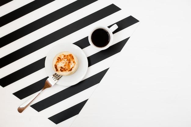 Elegante espacio de trabajo minimalista con taza de café y panadería.