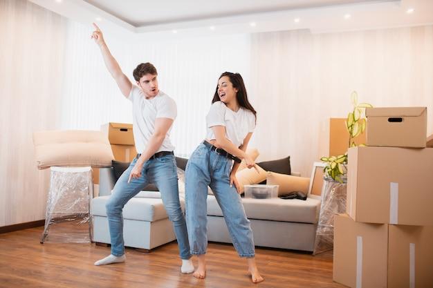 El elegante esposo y la esposa se divierten y se trasladan a su propio apartamento juntos, el concepto de reubicación. joven pareja feliz baila en la sala de estar cerca de cajas de cartón entretiene en el día de la mudanza,