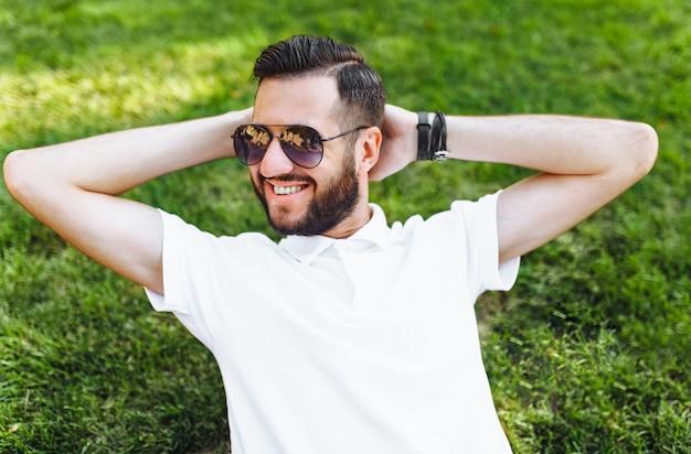 Elegante estudiante hipster con camisa blanca, descansando en el césped del parque, de buen humor