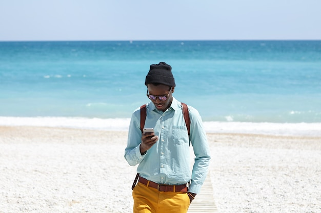 Elegante estudiante de piel oscura con mochila con ropa de moda de pie en el paseo marítimo después de caminar por la mañana en la playa desierta