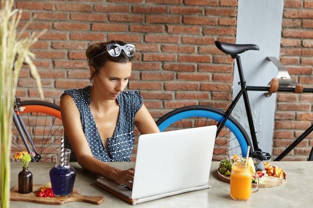 Elegante estudiante de teclado en la computadora portátil, mirando la pantalla con expresión seria y concentrada mientras se prepara para los exámenes