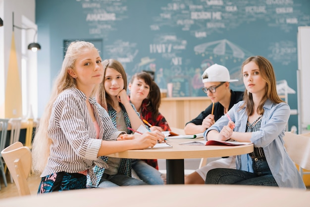 Elegante estudiantes sentados en el escritorio