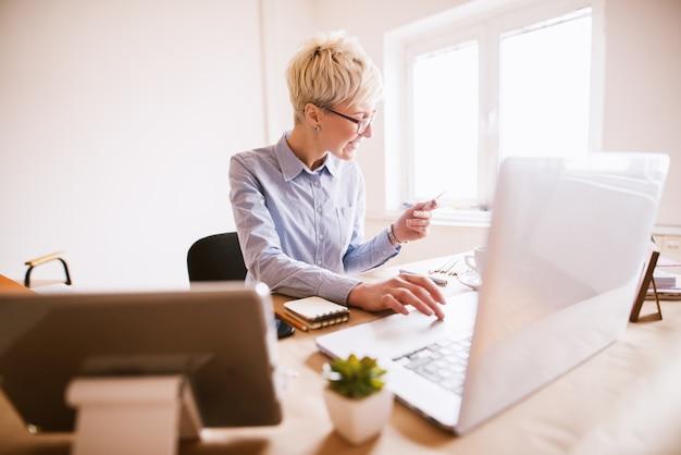 Elegante exitosa mujer de negocios comprando en línea con la tarjeta mientras está sentado en la hermosa oficina brillante.