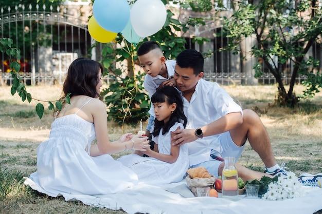 Elegante familia asiática celebrando el cumpleaños de su niña en un parque con un pequeño pastel. los padres y sus hijos vestidos de blanco a la sombra de un árbol.