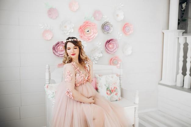 Elegante futura madre posando en vestido largo