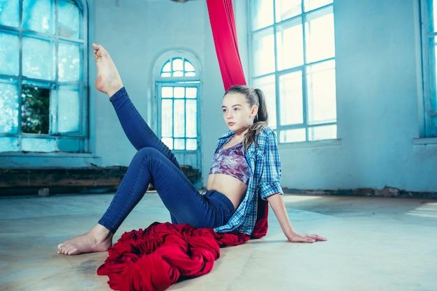 Elegante gimnasta descansando después de realizar ejercicio aéreo en el desván