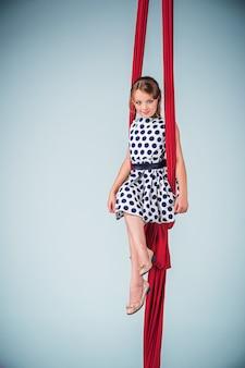 Elegante gimnasta sentada con telas rojas