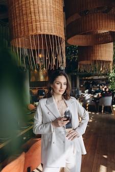 Elegante y glamurosa mujer con copa de vino tinto en restaurante.