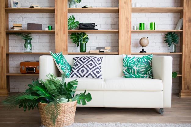 Elegante habitación interior con sofá blanco y hojas tropicales.
