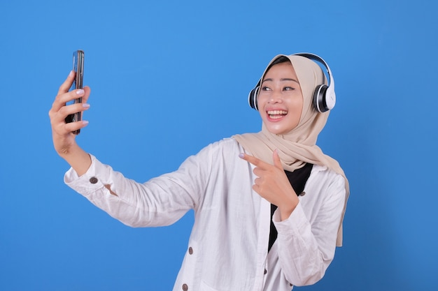 Elegante hermosa chica escuchando música mientras toma una foto de sí misma. mujer entusiasta con teléfono para selfie