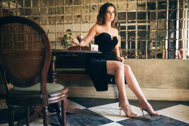 Elegante hermosa mujer sentada en un café vintage con vestido de terciopelo negro, vestido de noche, dama elegante rica, tendencia de moda elegante, mirada seductora sexy, figura flaca atractiva con piernas largas en tacones