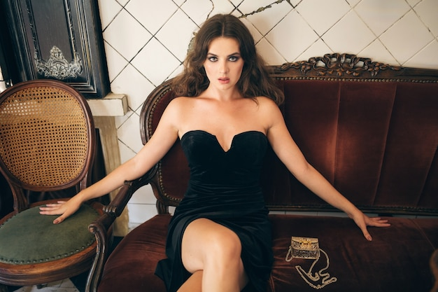 Elegante hermosa mujer sentada en un café vintage en vestido de terciopelo negro, vestido de noche, dama con estilo rico, tendencia de moda elegante, look sexy