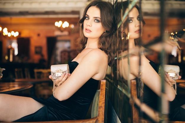Elegante hermosa mujer sentada en un café vintage con vestido de terciopelo negro, vestido de noche, rica dama elegante, elegante tendencia de moda, esperando una cita, sosteniendo un pequeño bolso dorado en la mano