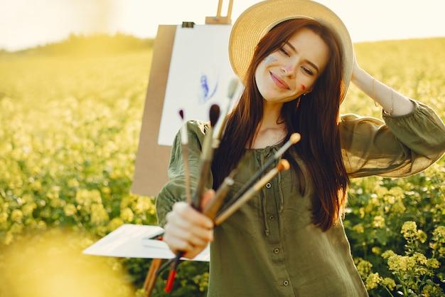 Elegante y hermosa niña pintando en un campo