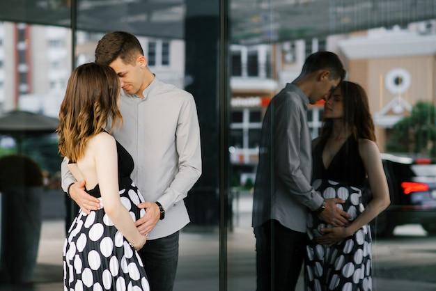 Elegante hermosa pareja de enamorados embarazadas en ropa de blanco y negro abrazo