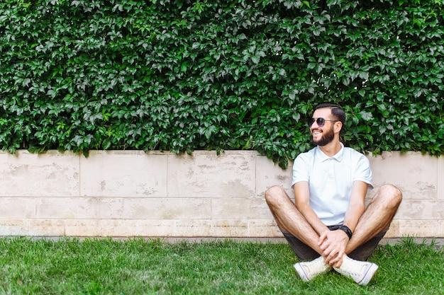 Elegante hipster con barba y una camiseta blanca, sentado en el césped en la pared verde de hoja caduca