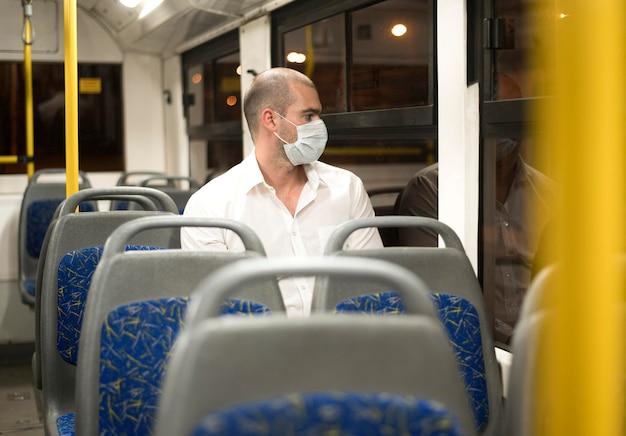 Elegante hombre adulto viajando en autobús con máscara médica