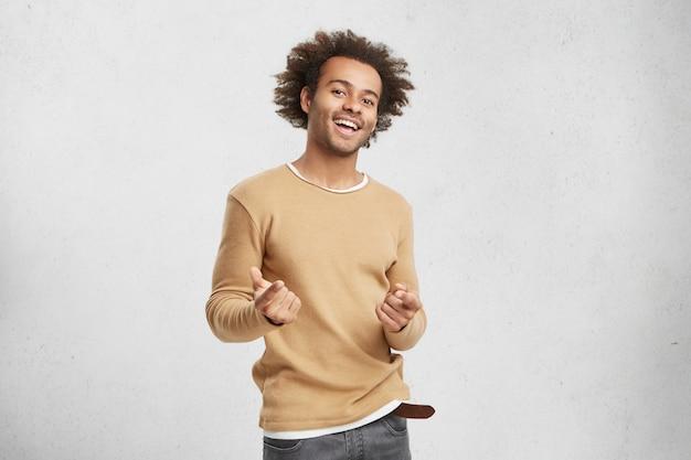 Elegante hombre afroamericano feliz viste ropa casual, apunta a la cámara con los dedos índice