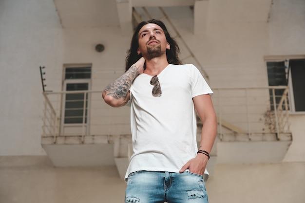 Elegante hombre barbudo con cabello largo y tatuajes posando