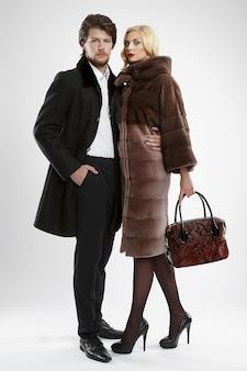 Elegante hombre y glamour mujer en abrigo de piel posando