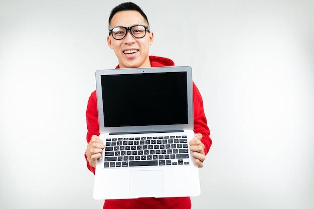 Elegante hombre morena muestra una pantalla de portátil en blanco en manos sobre un fondo blanco de estudio