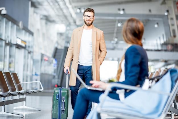 Elegante hombre de negocios en el abrigo de negocios de reunión en la sala de espera del aeropuerto