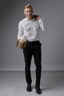 Elegante hombre de negocios con caja de regalo