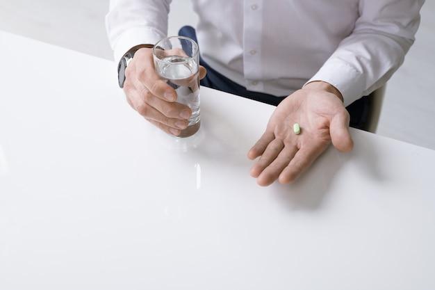 Elegante hombre de negocios con camisa blanca sosteniendo un vaso de agua y analgésico mientras está sentado junto al escritorio y va a tomar la píldora