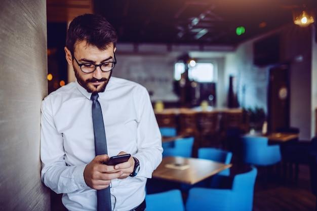 Elegante hombre de negocios guapo con barba caucásica en camisa, corbata y anteojos apoyado en la pared en la cafetería y usando el teléfono inteligente para leer o enviar mensajes