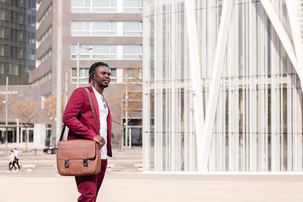 Elegante hombre de negocios negro con maletín camina por el centro financiero de la ciudad, copia espacio para texto