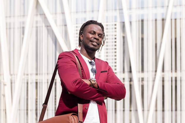 Elegante hombre de negocios negro con maletín posando con los brazos cruzados en el centro financiero de la ciudad, copia espacio para texto