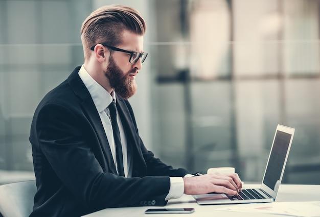 Elegante hombre de negocios se sienta en una computadora y funciona. un hombre de traje se sienta en un escritorio de la oficina.