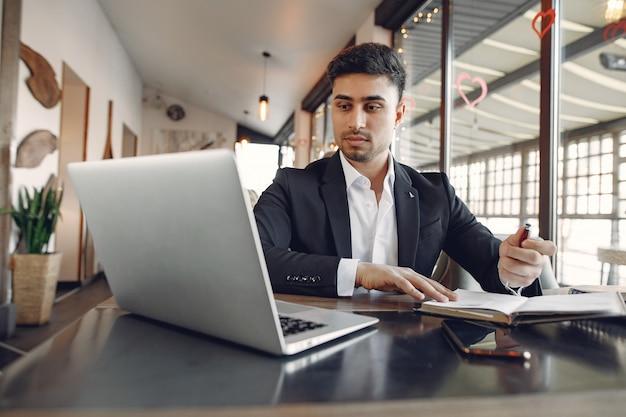 Elegante hombre de negocios trabajando en un café y usar la computadora portátil