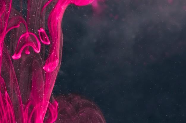 Elegante humo violeta en pantalla negra.