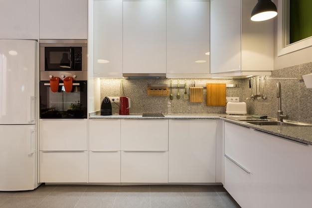 Elegante interior de cocina moderna con mesa de mármol y electrodomésticos.