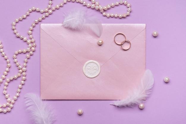 Elegante invitación de boda con perlas y anillos de compromiso